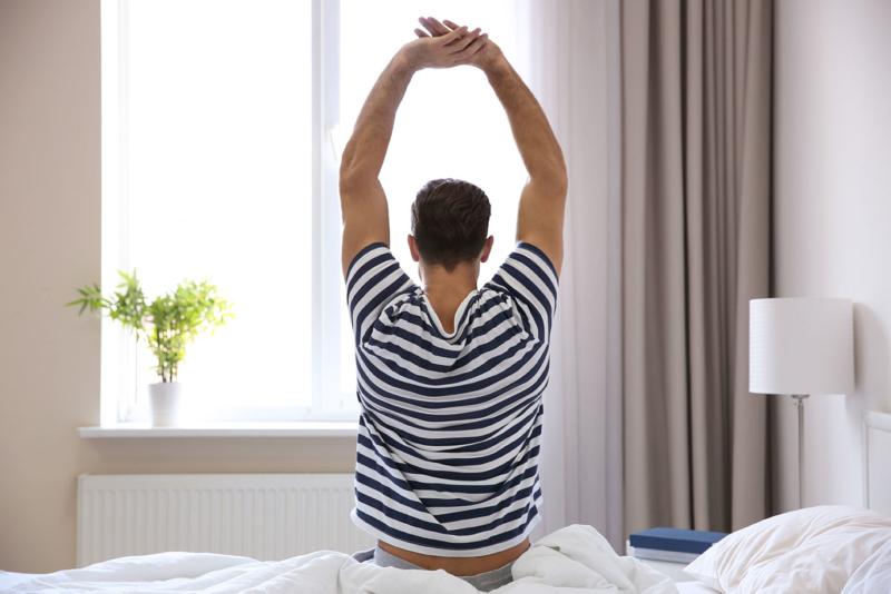Photo d'un homme venant de se réveiller et s'étirant, un atelier pour optimiser les moments de la journée pour se ressourcer, limiter son stress et être plus efficace dans son travail
