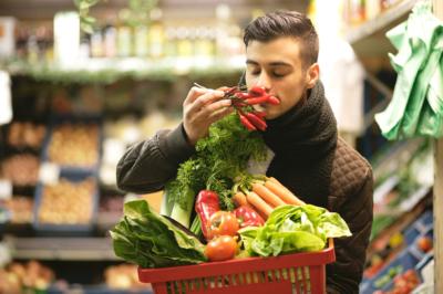 Photo d'un homme faisant ses courses avec un panier remplis de fruits et legumes, homme sent l'odeur de ses legumes, nos collaborateurs peuvent, à travers cette animation, découvrir une manière saine de consommer