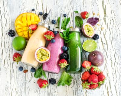 Photo de smoothies et de fruits poses sur une table, faire le plein d'énergie et de vitamine grâce a des fruits, tout au long de la journée