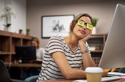 Photo d'une femme dormant avec des post it sur les yeux, des yeux sont dessines sur les post it, la sieste au travail permet aux collaborateurs de se ressourcer pour travailler efficacement