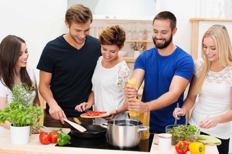 Photo d'hommes et de femmes cuisinant tous ensemble dans une cuisine, un moyen pour que les travailleurs améliorent la qualité de leur repas et adoptent une alimentation saine et équilibrée