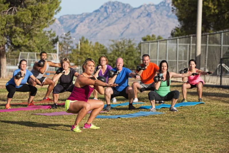 Photo d'une coach entrainant un groupe de personne au cross training en extérieur, séance permettant aux travailleurs de developper leur capacité physique tout en étant à l'extérieur