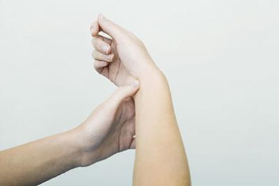 Photo des mains d'une personne faisant pression sur un point a l'intérieur de son poignet, technique de relaxation pour le bien-être au travail, réduction du stress