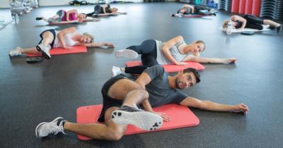 Photo de personnes s'entrainant sur des tapis de sport dans un gymnase, un outil pour developper sa condition physique