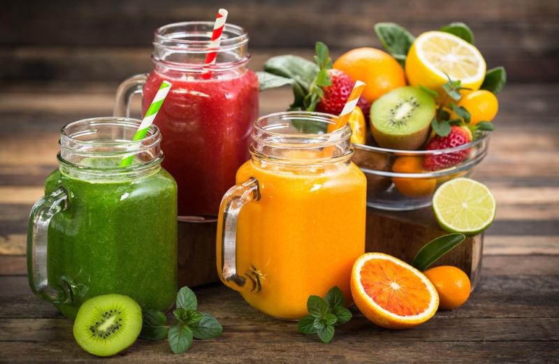 Photo de jus de fruits et de fruits poses sur une table en bois, apprendre à optimiser sa consommation de fruits au cours de la journée