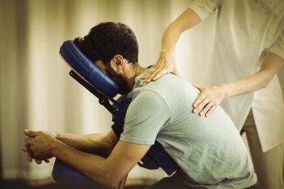 Photo d'un homme massé sur une chaise, le massage amma permet à nos collaborateurs de réduire leur niveau de stress