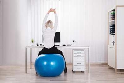 Photo d'une dame s'etirant à son poste de travail en etant assise sur une swissball, les pauses actives, un moyen pour se ressourcer et se reposer efficacement