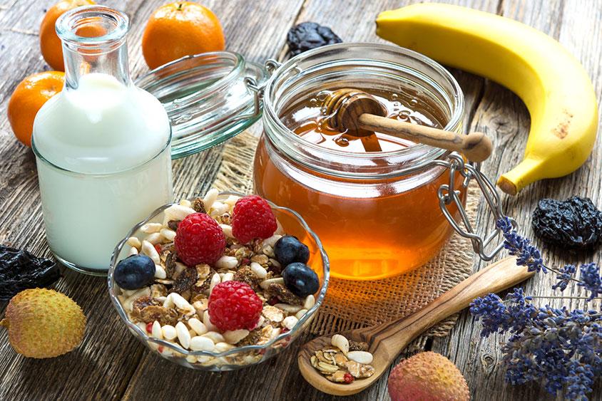 Image d'un petit déjeuner equilibre pose sur une table, avec un banae des cereles des fruits rouges du lait du miel des clementines et des litchis, composer un petit déjeuner solide permet de poser les bases d'une journée de travail efficace