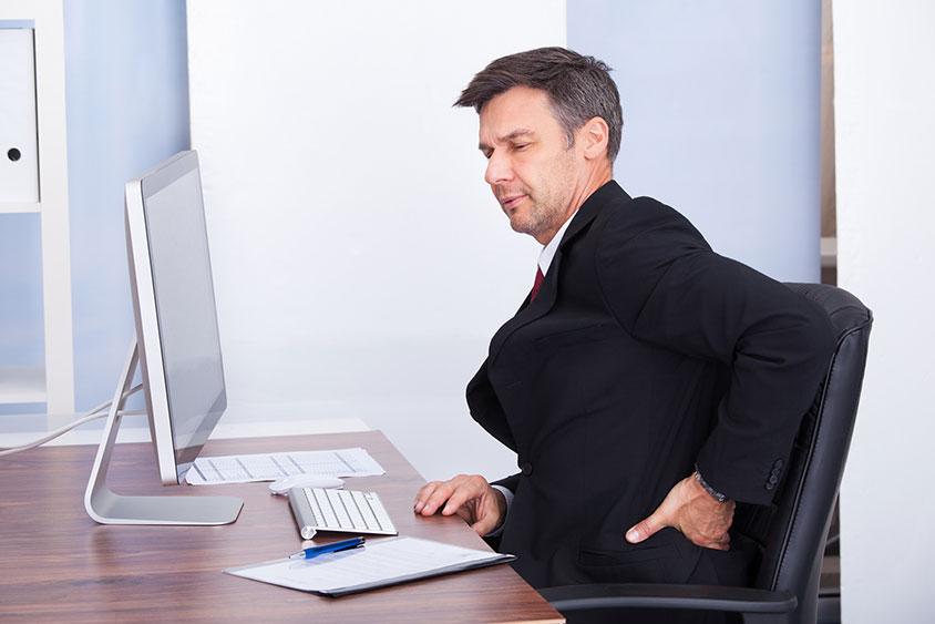 Photo d'un homme assis a son bureau ressentant une gene a cause d'un mal de dos, donner les outils à l'employé afin d'écarter les trouble musculosquelettique ou TMS