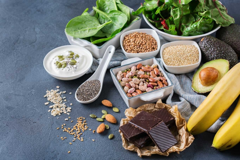Photos d'ingredients poses sur une table, avec du chocolat, de la creme, de la salade, des graines et une cuillere, soulager ses maux à travers la connaissance des bienfaits des aliments