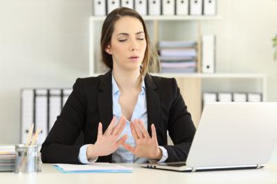 Photo d'une dame respirant et essayant de se relaxer a cause d'une douleur au coeur, un outil de diminution du stress pour permettre au collaborateurs de mieux vivre et travailler au quotidien