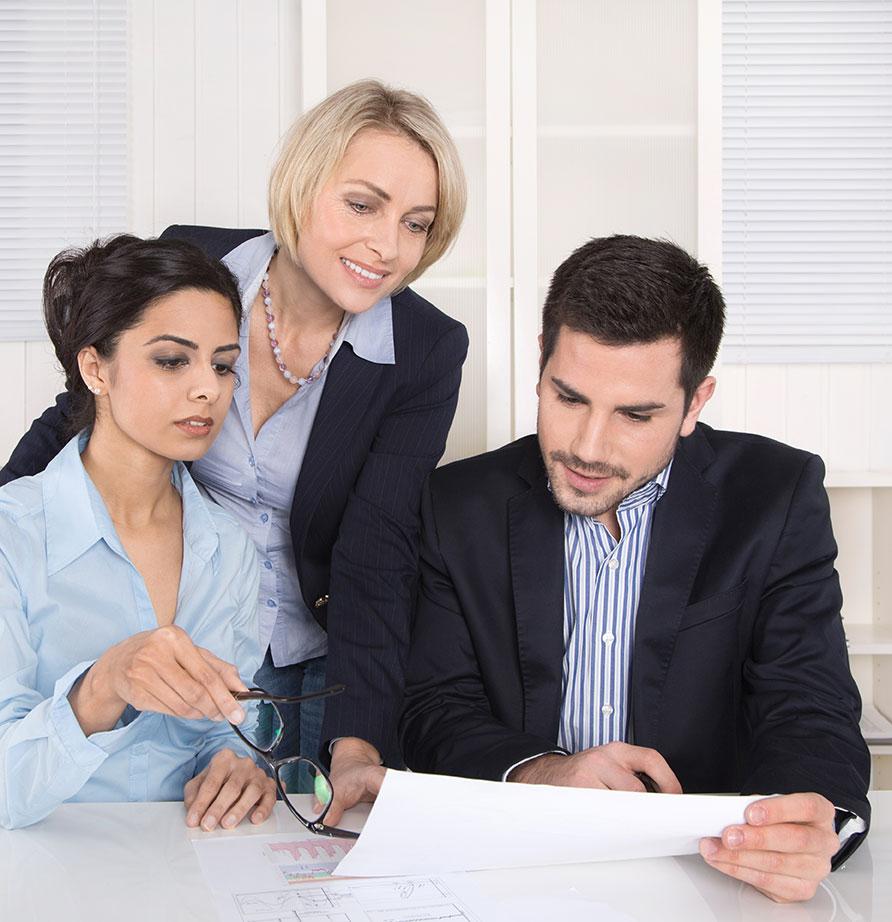 Photo de trois collegues discutant d'un projet de travail dans la bonne humeur, un outil pour que les employés atteignent une efficacité dans la communication au travail