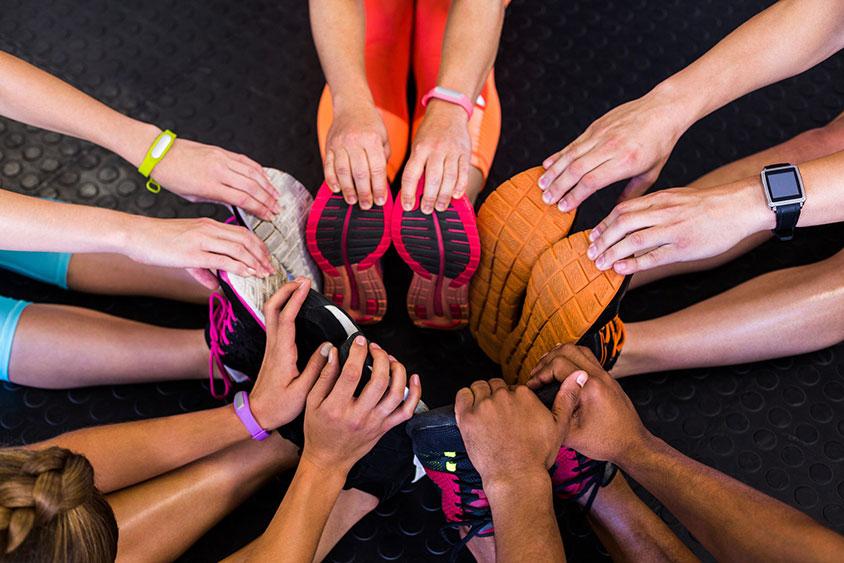 Photo des jambes d'un groupe de personnes s'etirant en cercle, mise en place de moyens pour pousser les employés à reprendre ou recommencer le sport