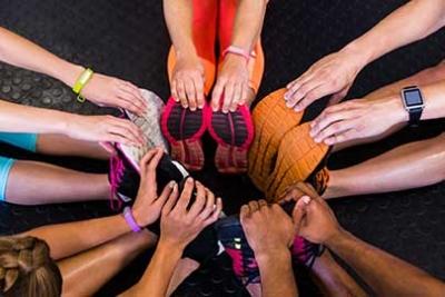 Photo d'un cercle de personnes s'etirant en se tenant les pieds avec les mains, reprendre ou adopter une pratique régulière du sport