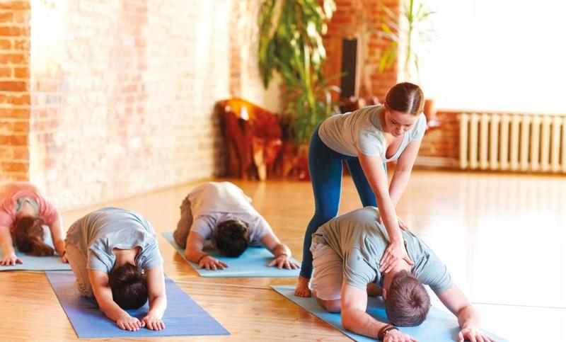 Photo d'une coach s'occupant du dos de quatre personnes faisant du sport, un moyen d'optimiser la prévention des problèmes de dos
