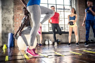 Photo d'un groupe de personnes s'entrainant dans un gymnase avec des echelles, des ballons et des poids, afin de developper l'activité physique pour se sentir mieux au quotidien