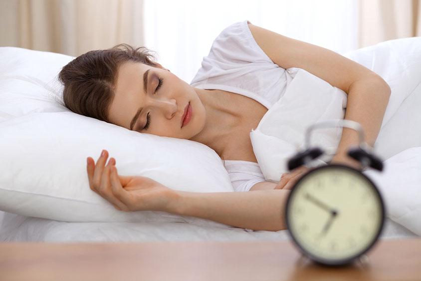Photo d'une femme dormant tranquillement dans son lit a cote de son reveil, favoriser son endormissement optimise la récupération et est essentiel pour avoir de l'énergie pour une journée au bureau