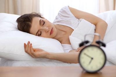 Photo d'une femme dormant dans son lit a cote de son réveil, favoriser son endormissement pour optimiser sa récupération et son repos durant la nuit