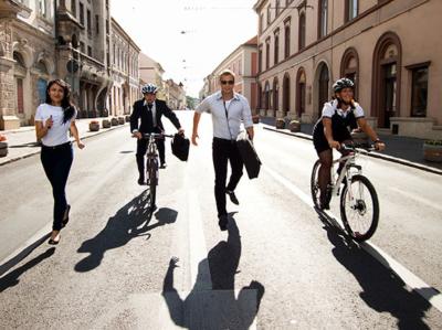 Photo de quatre travailleurs en chemise courant et faisant du velo sur la route en ville, développer ses capacités mentales, limiter son stress pour performer au travail