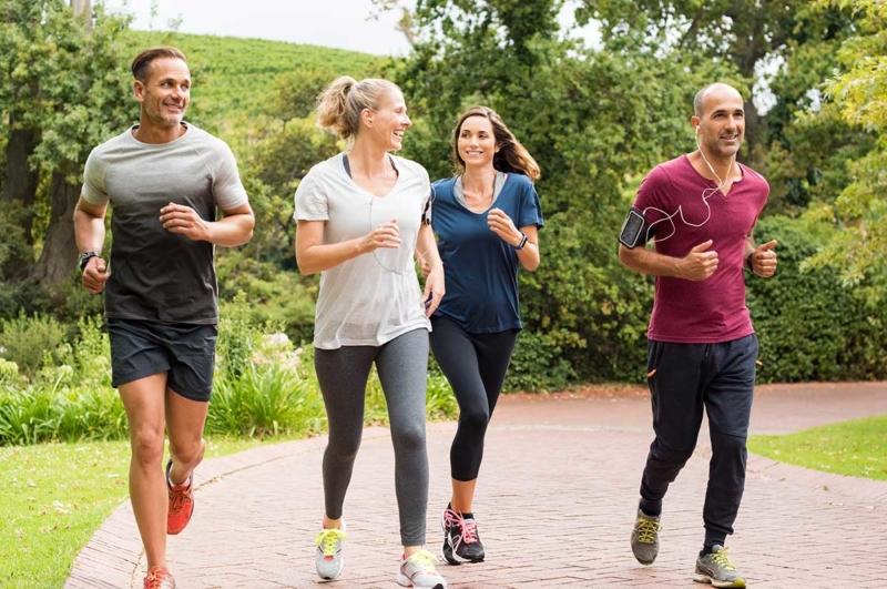 Photo de quatre personnes faisant un footing dans un parc et parlant ensemble, ou outils pour donner envie de s'engager au quotidien
