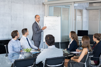 Image d'un homme parlant et presentant un pitch devant un groupe de travailleurs, prendre confiance en soi au travail