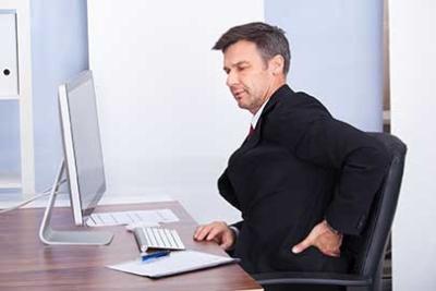 Photo d'un homme travaillant à son bureau et semblant dans l'inconfort à cause de soucis de dos, adopter les bonnes postures pour que nos collaborateurs limitent leurs problèmes de dos