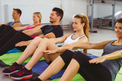 Photo d'un groupe travaillant leurs abdos dans un gymnase, les employés acquièrent une meilleure connaissance de leur corps