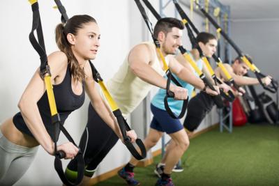 Photo d'un groupe de personne faisant du sport en salle avec des sangles, un outil pour que nos collaborateurs puissent développer leur capacités physique comme l'équilibre ou le système cardio vasculaire