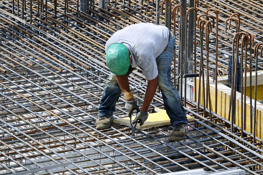 Photo d'un homme travaillant sur chantier dans une position inconfortable, un outil pour permettre à nos collaborateurs de travailler dans des conditions agréables et on aggressive ou dangereuse pour le corps et le dos