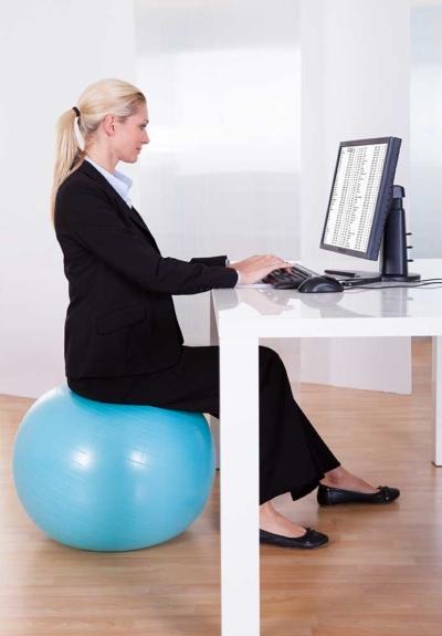 Photo d'une femme assise sur une swissball et travaillant sur son ordinateur, un moyen d'agir pour sa santé durant le travail sur ordinateur