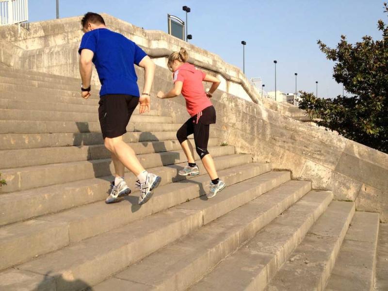 Photo d'un homme et d'une femme courant dans des escalier en exterieur, se défouler et se dépasser physiquement, un outil pour améliorer l'endurance et l'équilibre, se sentir mieux