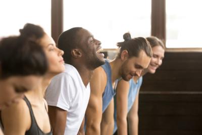 Photo de 5 personnes en tenue de sport rigolant ensemble, permettre à nos collaborateurs de soulager leur stress et d'oxygéner leur corps